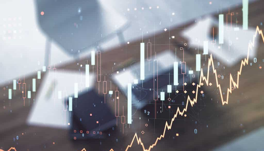 Growing financial graph on desktop background with laptop. Multi exposure. Stock market concept